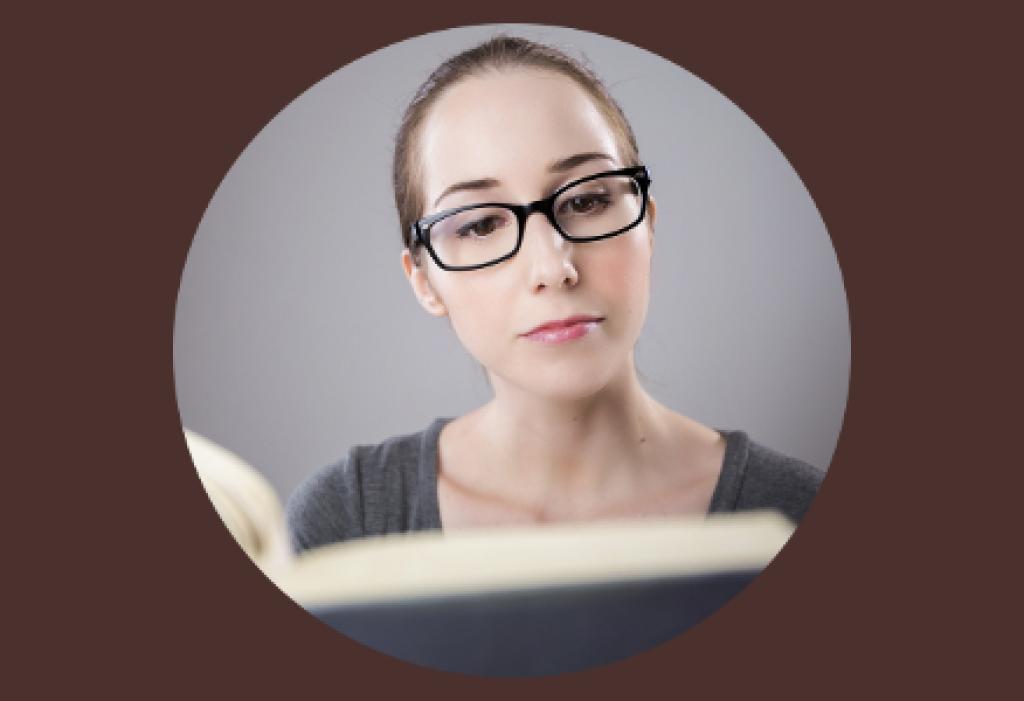 Eine Frau mit Brille liest ein Buch. Dabei schaut sie sehr konzentriert auf das Geschriebene.