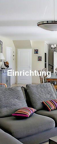 Die Einrichtung. Ein Wonzimmer mit einer grauen Couch und roten Kissen.