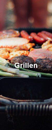 Auf dem Grill befinden sich mehrere Fleischsorten und Spargel.